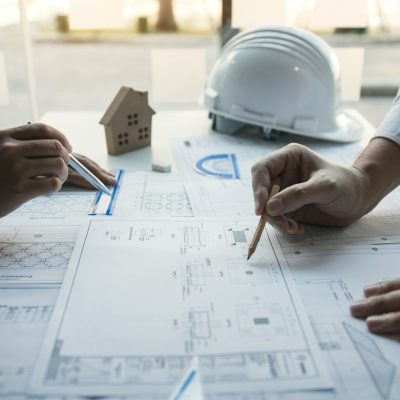 architect working at construction site and compass drawing pointing on blueprint