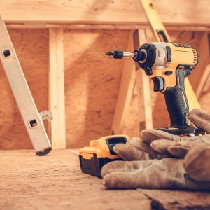 Drill Driver and Safety Gloves Inside Wooden Building Construction Site. Construction Industry Job Theme.